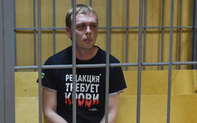 Russian investigative journalist Ivan Golunov, charged with attempted drug-dealing, sits inside a defendants' cage during a hearing at a court in Moscow on 8 June 2019.