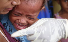 A child is immunised for measles in Vanuatu following Cyclone Pam.