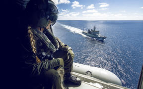 Leading Helicopter Loadmaster Steph Roberts watches HMNZS Wellington as the 6SQN SH-2G(II) Seasprite Helicopter flies nearby.