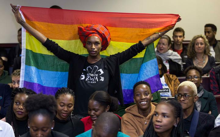 An activist holds up a rainbow flag to celebrate inside Botswana High Court in Gaborone on June 11, 2019. - Botswana's Court ruled on June 11 in favour of decriminalising homosexuality, handing down a landmark verdict greeted with joy by gay rights campaigners. (Photo by Tshekiso Tebalo / AFP)