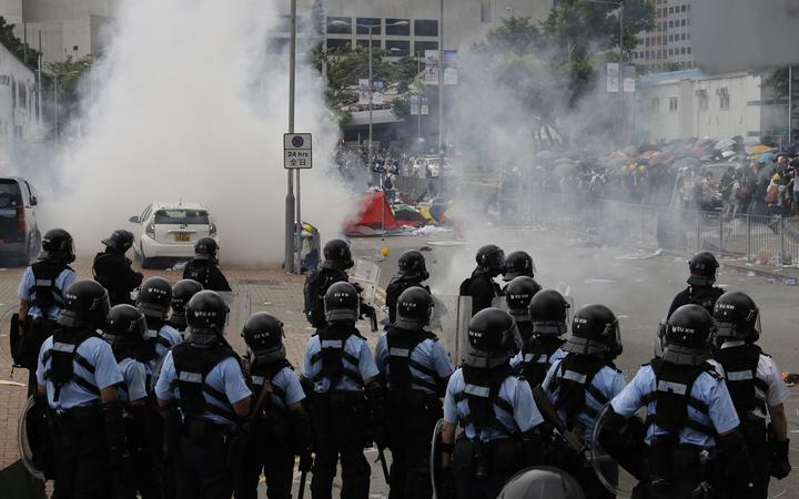 Riot police fire tear gas to protesters outside the Legislative Council in Hong Kong, Wednesday, June 12, 2019.