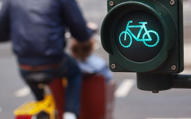 A cyclist passes a green cycling traffic light in a city.