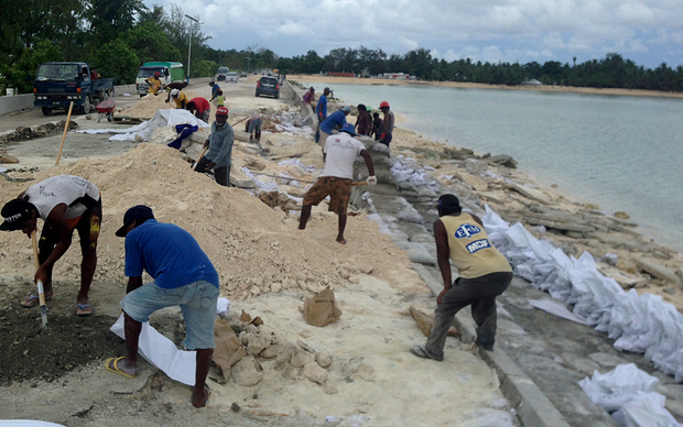 Sand bagging the beach to stop erosion in Tarawa, Kiribati.