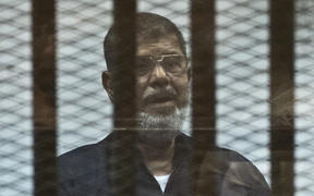 Mohamed Morsi stands behind the bars during his trial in Cairo in 2015.