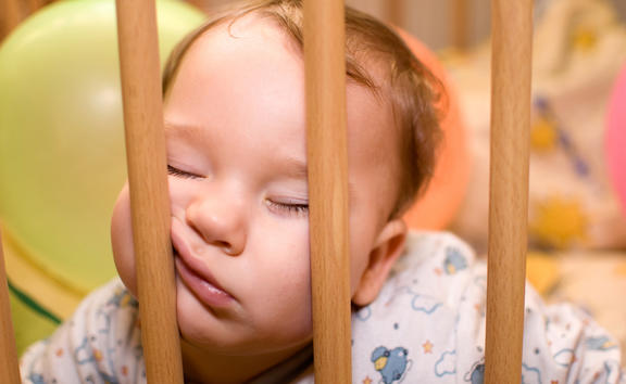 Baby sleeps with funny face in the playpen
