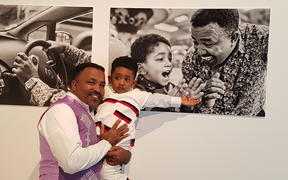 Niguisse Fenja with his photos and son Emmanual.