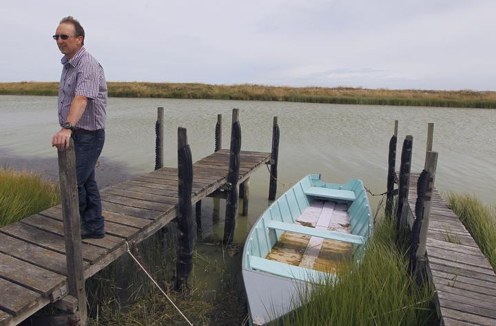 Man stands on small wooden jetty on edge of murky river by small wooden boat