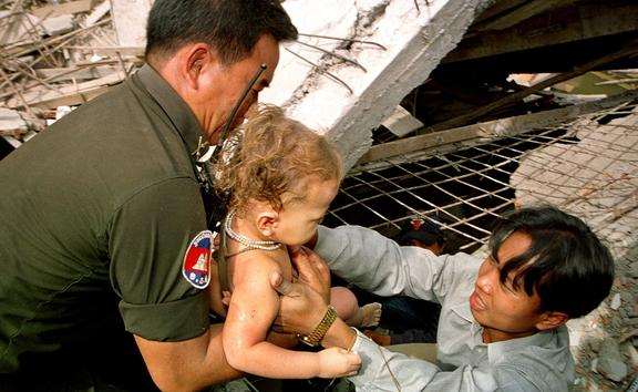A Cambodian rescuer helped by a policeman, removes a baby from the wreckage as he survived the collapse of a building in Phnom Penh.