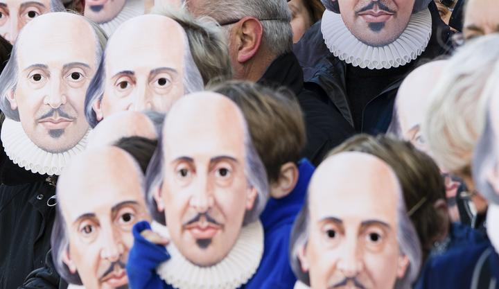 People wearing William Shakespeare masks line the street in Stratford-upon-Avon during a parade to mark 400 years since the bard's death.