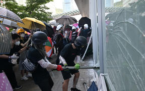 Protesters attempt to break a window at the government headquarters in Hong Kong.