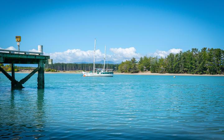Wharf at Mapua with slopp moored in channel of Waimea Estuary on Tasman Bay in South Island New Zealand.