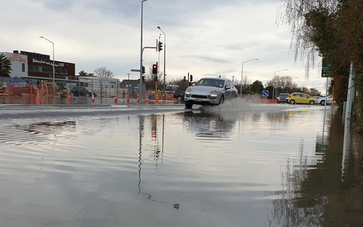 A car travels through floodwater on Innes Rd, Christchurch after a blown watermain.