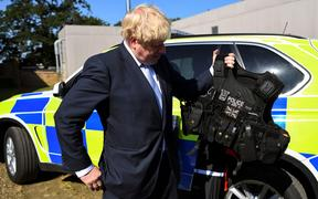 Conservative MP and leadership contender Boris Johnson holds a bulletproof vest during his visit to the Thames Valley Police Training Centre.