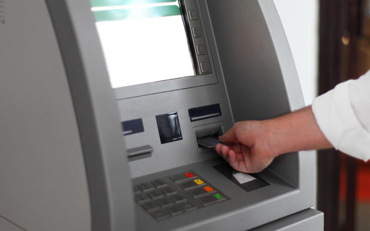 Close up of hand of a man using banking machine