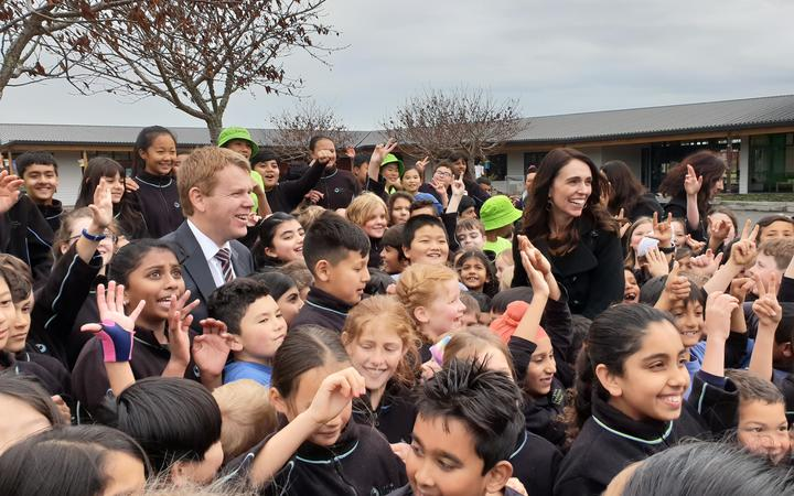 Education Minister Chris Hipkins and PM Jacinda Ardern with school students following today's announcement.