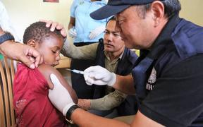 WHO Representative Dr Luo Dapeng administering the measles-rubella vaccine to a child in Jiwaka province.