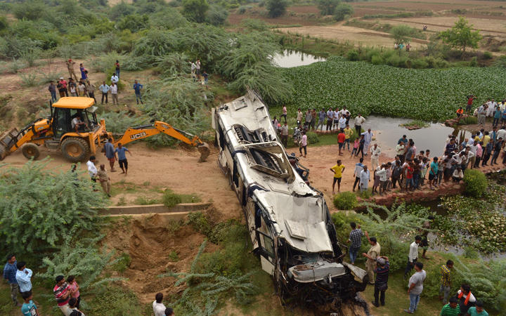 Onlookers and Indian police gather around the crumpled remains of a bus that crashed on the Delhi-Agra expressway, near Agra.