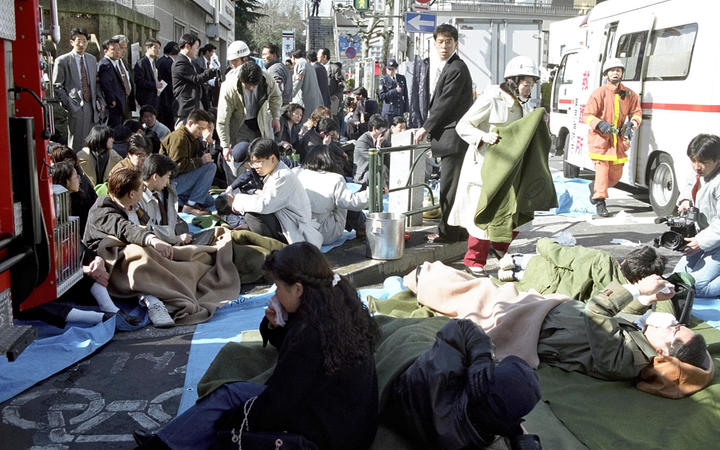 The passengers of subway lie down on a street at Hacchobori Station in Tokyo on 20 March, 1995 after a sarin attack.