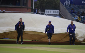 Groundstaff move the covers as rain stopped play during the 2019 Cricket World Cup first semi-final between India and New Zealand at Old Trafford in Manchester on July 9, 2019.
