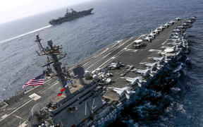Aircraft carrier USS Abraham Lincoln  and the Amphibious Assault Ship USS Kearsarge (LHD 3) sail in the Arabian Sea in May.