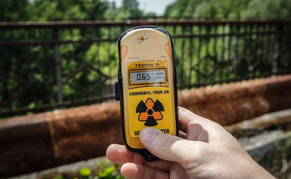 A visitor measures the level of radiation on the so-called Death bridge in the abandoned city of Pripyat, near the Chernobyl nuclear power plant, Ukraine, on 7 June 2019.