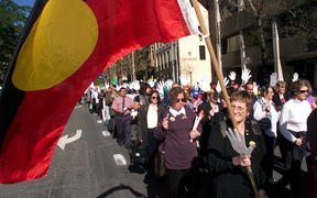 A woman waves an Aboriginal flag during a march to commemorate Sorry Day in Sydney 26 May 1999.