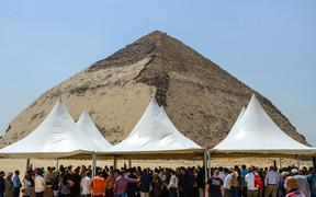 People gather during an inaugural ceremony in front of the Bent pyramid of King Sneferu, the first pharaoh of Egypt's 4th dynasty, in the ancient royal necropolis of Dahshur  south of  Cairo on July 13, 2019.