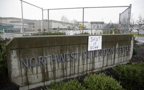 "A sign that reads ""shut it down"" is pictured at the Northwest Detention Center as people attend the People's Tribunal Against the Detention Center event in Tacoma, Washington on February 26, 2017. (Photo by Jason Redmond / AFP)"