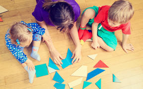 teacher and kids playing with geometric shapes, early learning