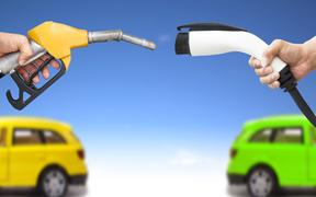 20231108 - electric car and gasoline car concept. hand holding gas pump and power connector for refuel