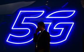 A man speaks on the phone next to a 5G hotspot sign displayed at the Mobile World Congress in Barcelona in February.