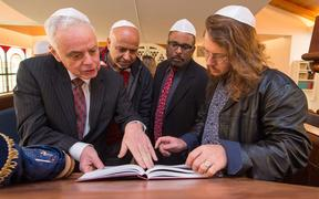 New Zealand Jewish Council president Stephen Goodman (front left) and Asher Levi Etherington (front right) show Muslim visitors a Torah at a Christchurch Synagogue.