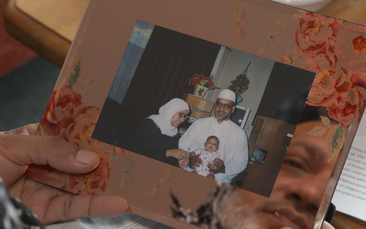Farid Ahmed holding an old photo of him with his wife Husna, who died in the 15 March shootings, and his daughter.
