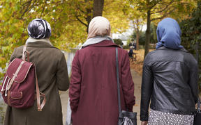 Muslim women walking in urban environment.