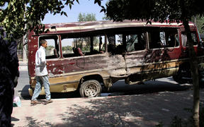 A boy walks past the wreckage of a bus following a suicide bombing in Kabul.
