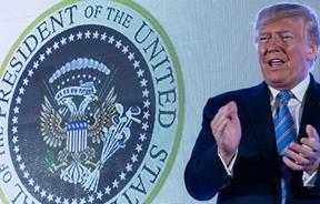 US President Donald Trump arrives to address the Turning Point USA's Teen Student Action Summit 2019 in Washington, DC. Trump stands in front of a presidential seal manipulated to make the eagle resemble Russia's two-headed version.