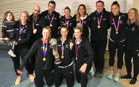 Silver Ferns Sharon Saunders, Ameliaranne Ekenasio and Jane Watson (front, L-R), Phoenix Karaka (rear, fourth from right), Karin Burger (rear, second from right) and team staff show off the Netball World Cup after landing at Auckland Airport.
