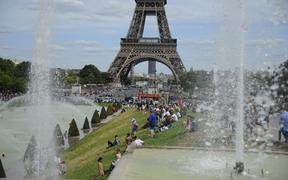 People in front the Eiffel Tower in Paris as temperatures degrees reach 41 Celsius.