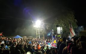 Thousands of people huddle around a small stage at Ihumātao enjoying a free concert.