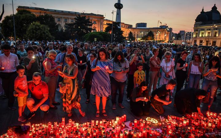 People light candles at a makeshift memorial site in front of the Romanian Ministry of Interior in Bucharest July 27, 2019 to commemorate Alexandra, the 15-year-old girl who has being murdered after she telephoned three times to report her own kidnapping.