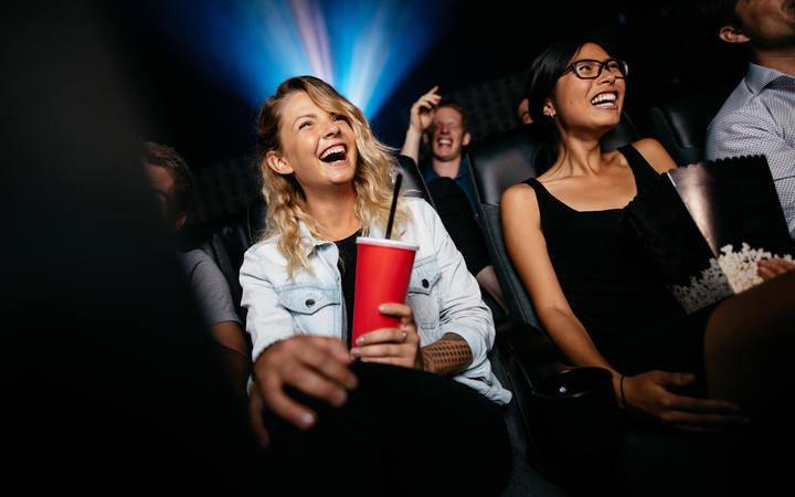 Young people laughing while watching film in movie theater.