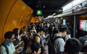 Commuters line up on a Mass Transit Railway (MTR) platform in Hong Kong on 30 July, 2019, after MTR services were resumed after being suspended by protesters demonstrating against a controversial extradition bill.