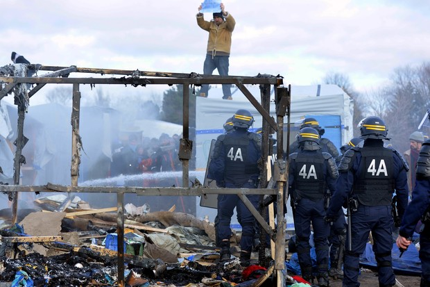 Camp occupants face anti-riot policemen at the Calais refugee camp.