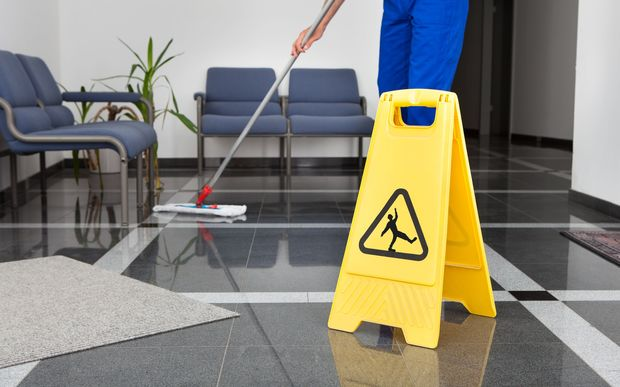A worker mops a floor next to a 'cleaning in progress' sign.