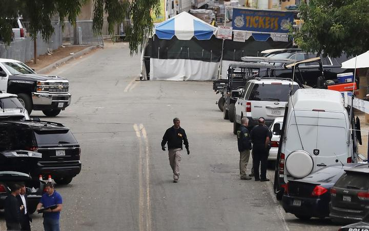 An FBI agent (C) walks near a ticketing booth for the Gilroy Garlic Festival two days after a mass shooting there.