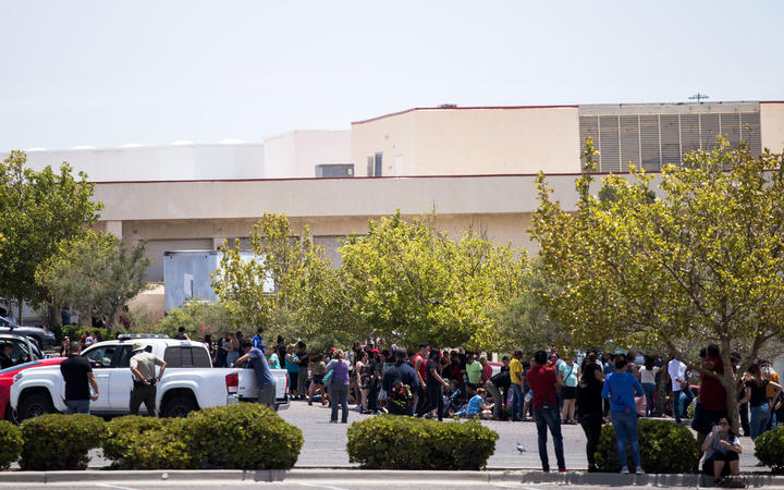 People evacuated from the mall where the shooting took place sit in a parking area.