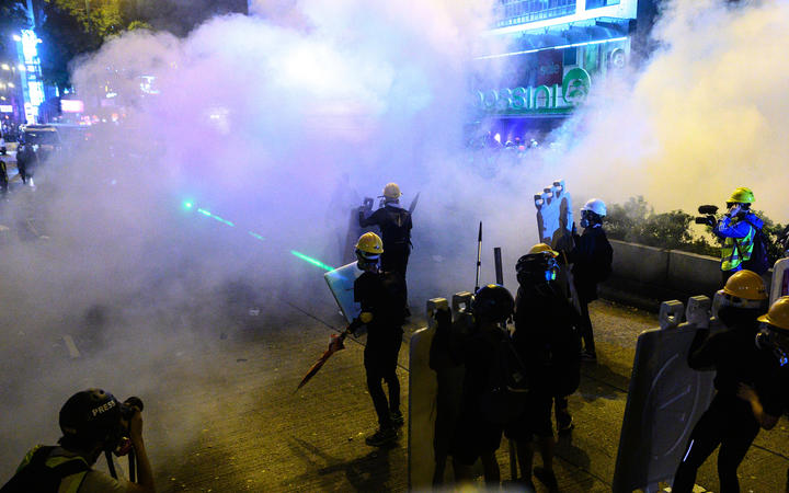 Protesters stand as police officers fire tear gas during a protest in Tsim Sha Tsui district of Hong Kong.