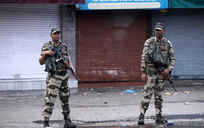Security personnel stand guard on a street in Jammu.