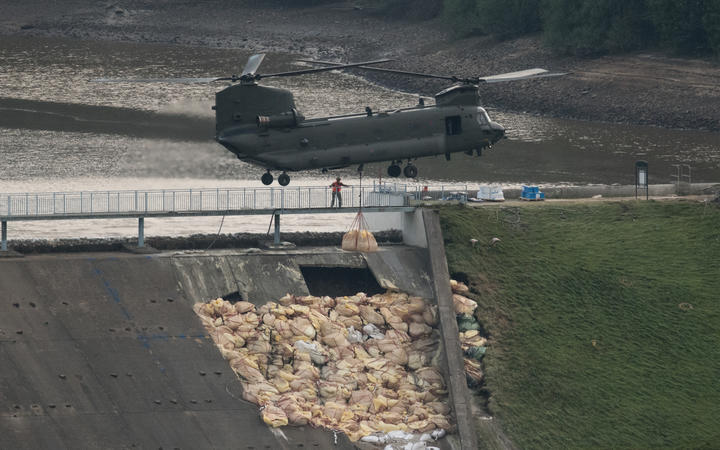 An RAF Chinook helicopter drops more bags of aggregate on the damaged section of spillway of the Toddbrook Reservoir dam above the town of Whaley Bridge in northern England on 4 August 2019.