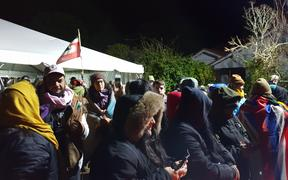 People gathered at Ihumātao on Monday evening after police deployed more officers to the scene.